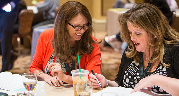A photo taken at a SpringBoard professional learning event shows two women seated side by side at a table smiling and talking as they look at a workbook together.