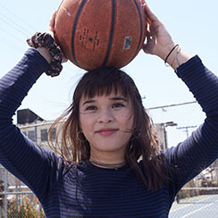 Student with a basketball over her head